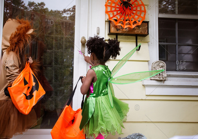Two kids ringing doorbell trick or treating