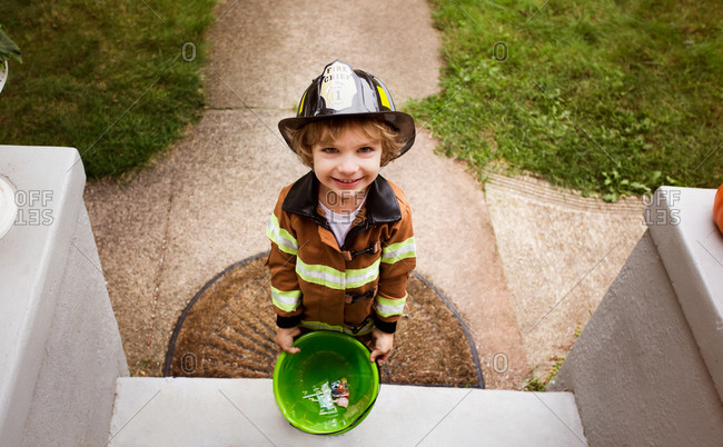 Kid in fireman costume on front step