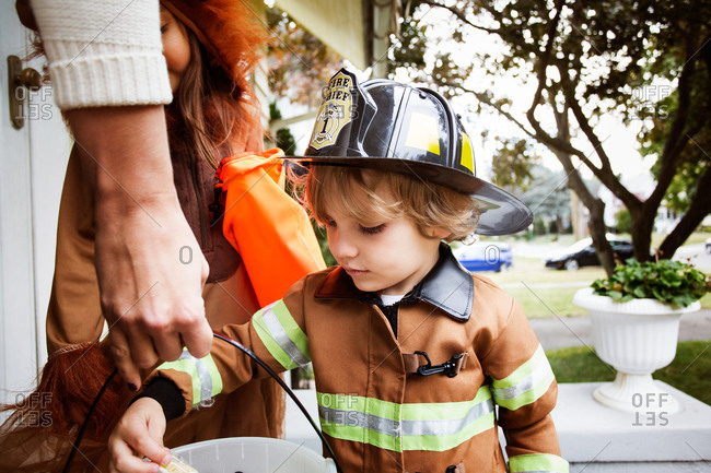 Boy in fireman costume grabbing candy
