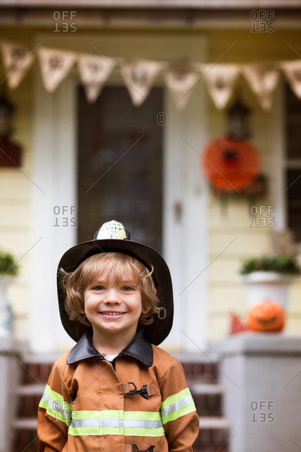 Boy in fireman costume in front of house