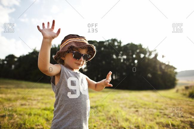 Little boy waving in a field