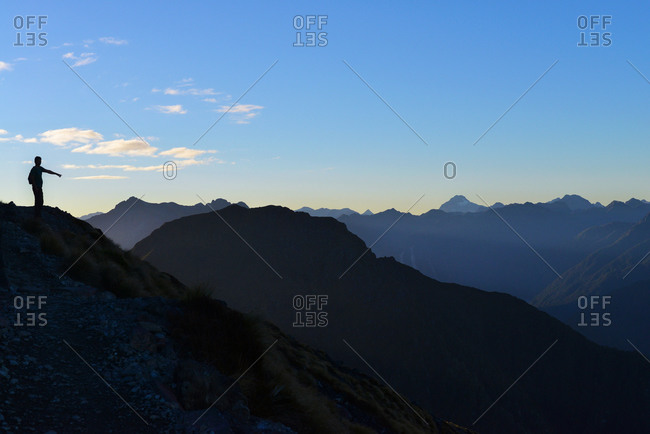 Silhouette of a person standing on top of a mountain