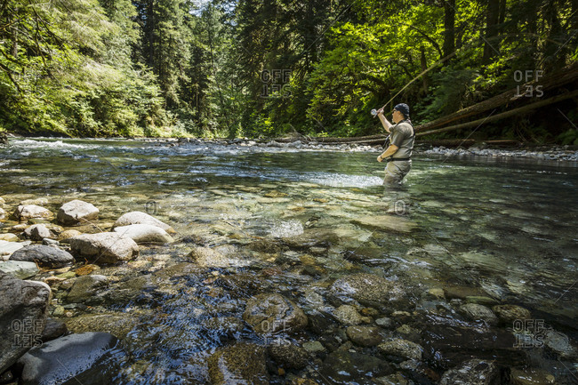 Man in river casting fishing line
