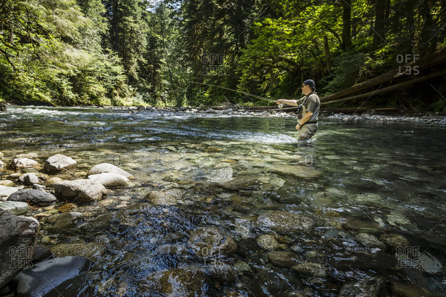 Man knee deep in river casting fishing line