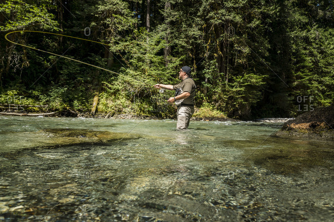 Man fishing in stream in waders