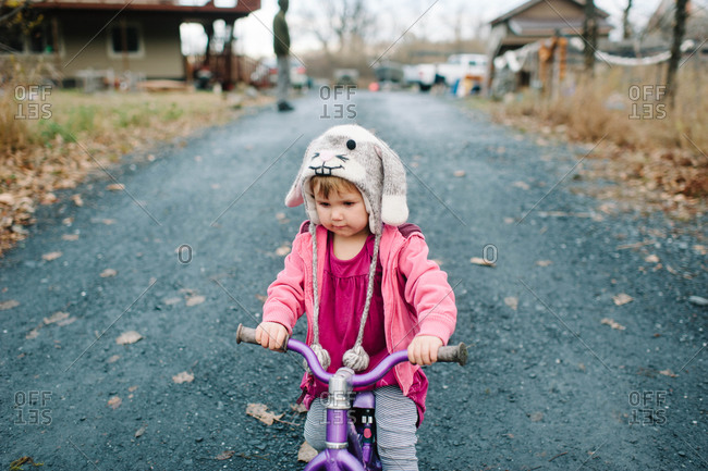 Girl riding trike in gravel driveway