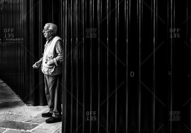 Venice, Italy - June 7, 2014: Elderly man standing in the back streets