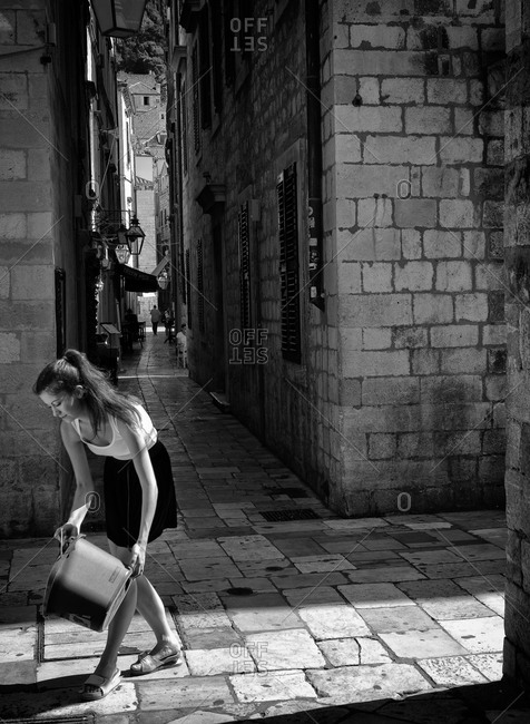 Dubrovnik, Croatia - June 18, 2012: Young woman emptying a bucket on a street