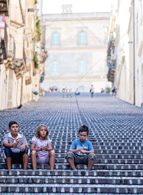 Sicily, Italy - September 10, 2011: Children sitting on a stairway with ice cream