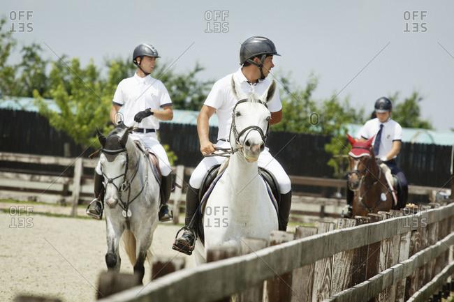 Men on horseback before show jumping