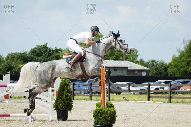 Man on horse jumping during competition