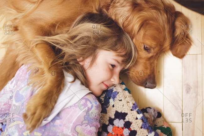 A golden retriever lays with a girl