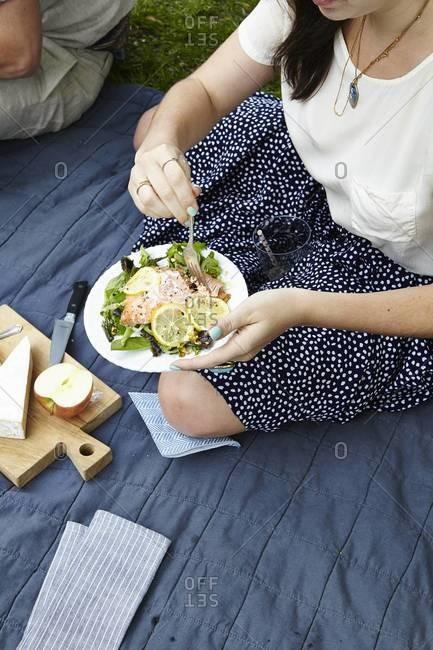 Woman having salmon salad on a picnic