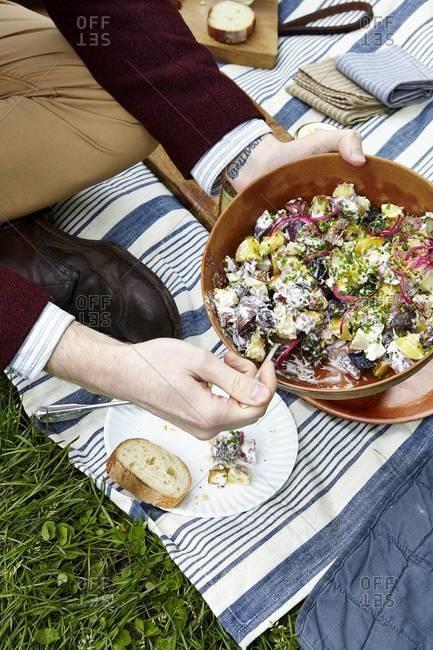 Man serving potato salad at a picnic