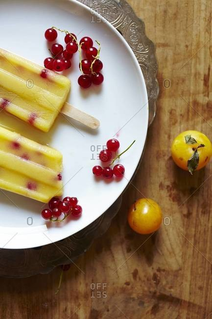 Mirabelle plum popsicles served with redcurrant on a plate