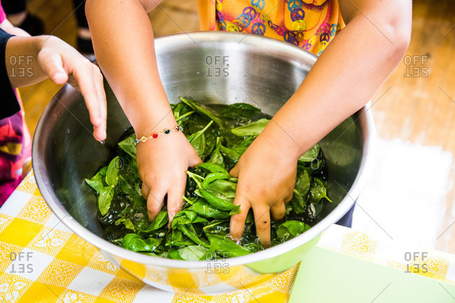 Child washing spinach in a bowl