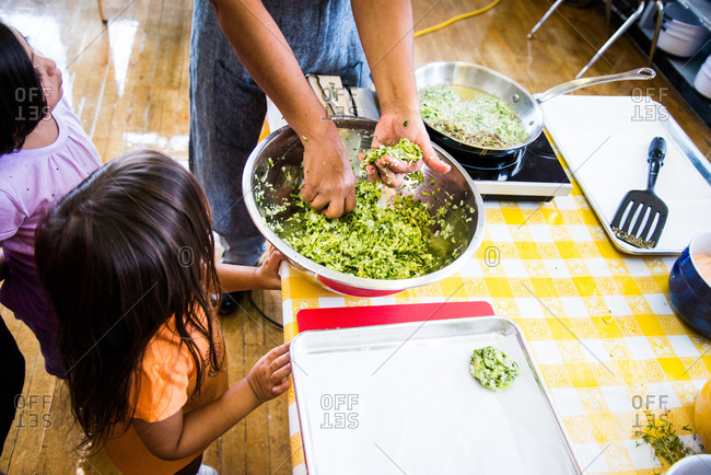 Children making zucchini fritters in a kitchen