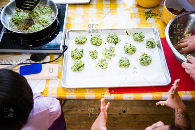 Kids making zucchini fritters