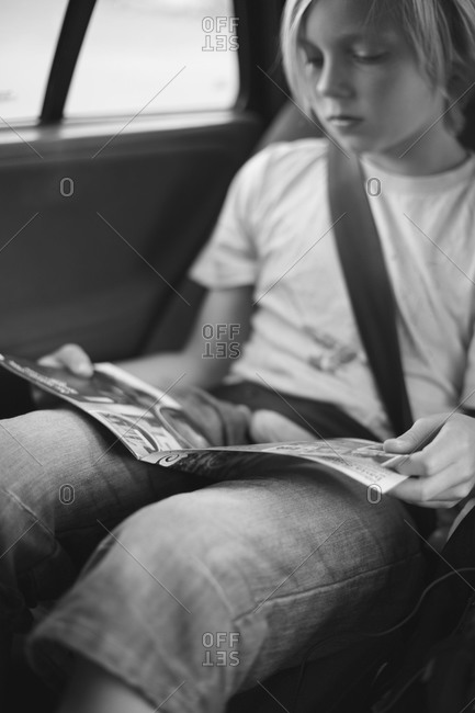 Boy reading magazine in car