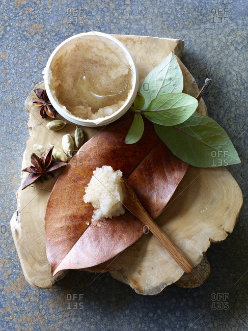 Body scrub paste in a bowl with leaves