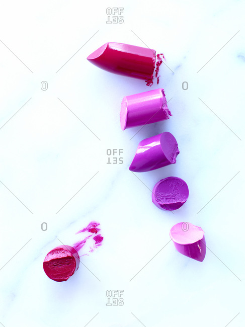 Pieces of lipstick on white background