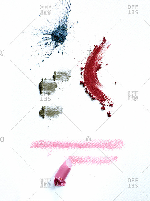 Lipstick and eye shadow smeared on white background