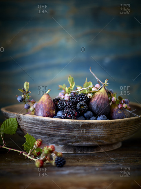 Various berries and figs in stone bowl