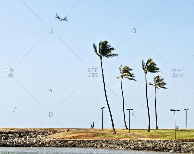Airplane flying over Magic Island during landing near Honolulu Airport