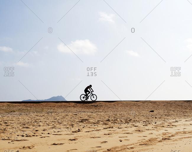 Man cycling on Magic Island with Diamond Head in background near Honolulu Hawaii