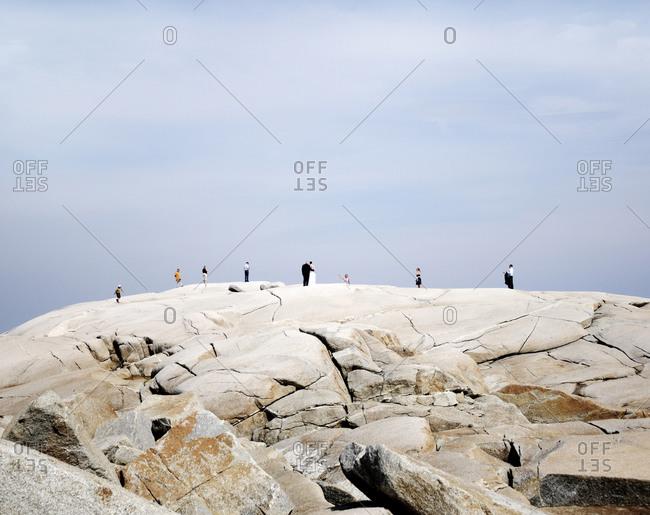 Tourists and a newlywed couple enjoy the view on rocks near Peggy's Cove Halifax, Nova Scotia, Canada