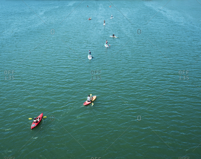 People in kayaks and on stand up boards paddling down a river near Austin, Texas