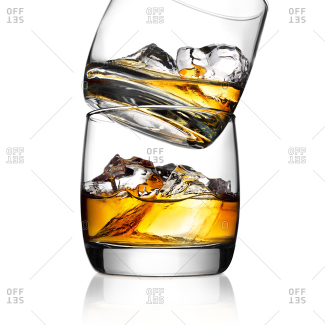 Two bourbon whiskey glasses stacked on top of each other with whiskey and ice inside