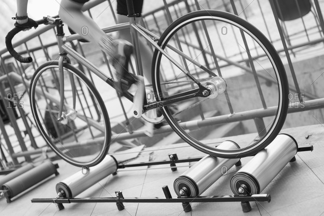 Low section of cyclist riding bicycle on rollers