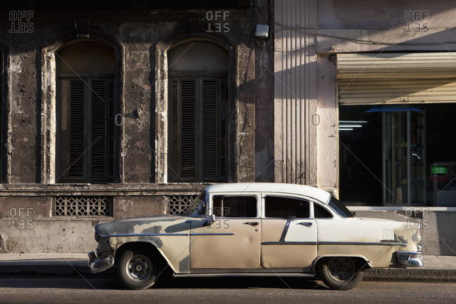 Old vintage car parked on street outside building  in Havana, Cuba