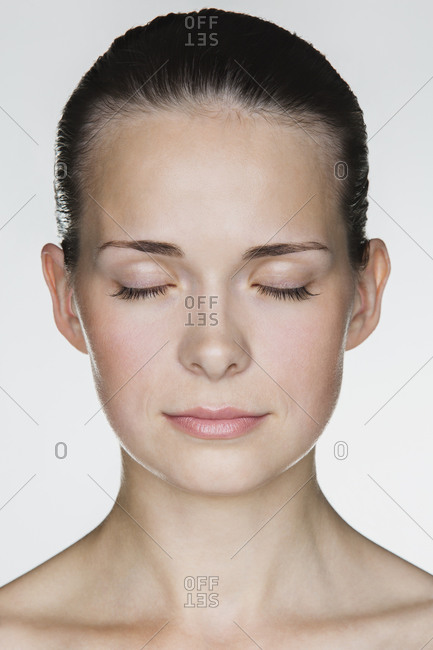 Close-up of  young woman with eyes closed against white background