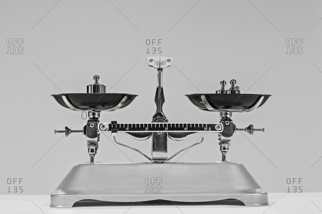 Vintage weighing scale and weights against gray background