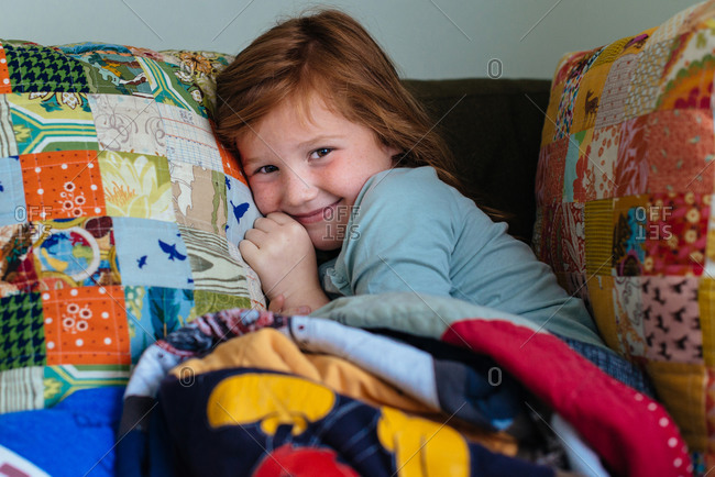 Portrait of girl curled up with patchwork blanket and pillow