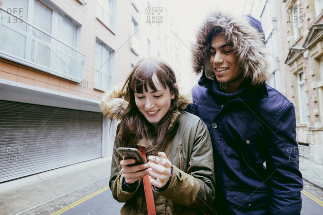 Young couple walking down street looking at phone