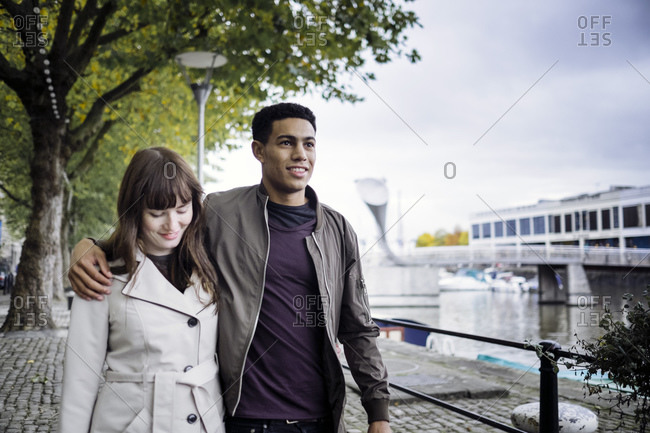 Couple strolling along river in Bristol