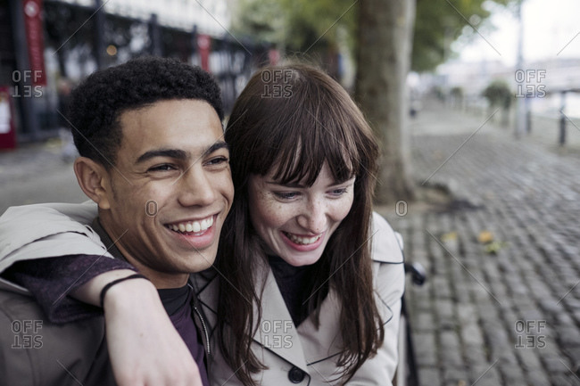 Couple sitting on bench laughing