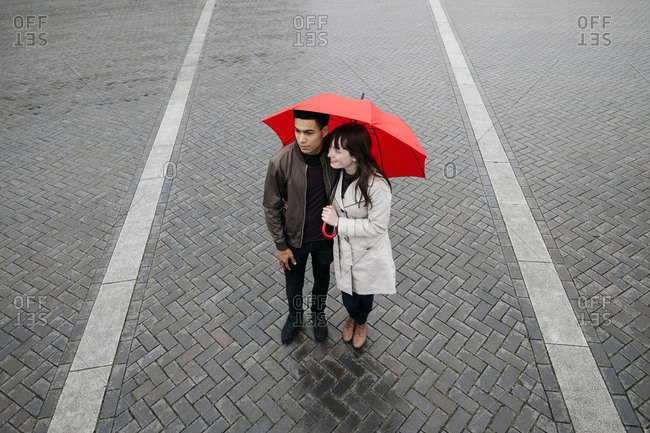 Couple standing in plaza with umbrella