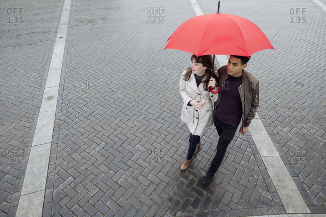 Couple with umbrella in plaza
