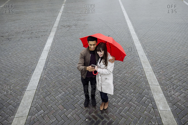 Couple looking at phone in plaza with umbrella