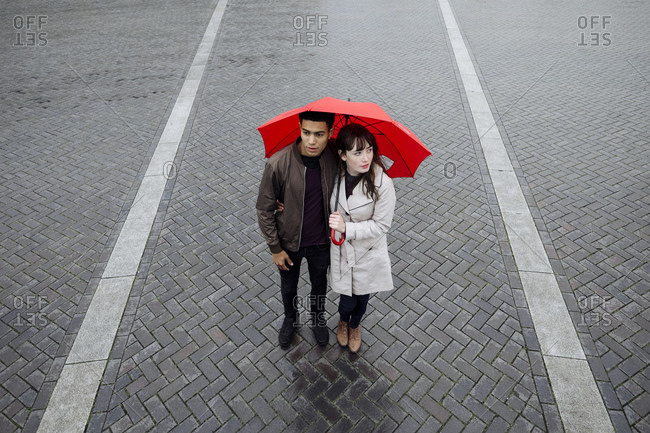 Couple in plaza with an umbrella