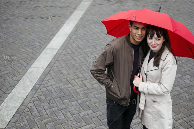 Couple embracing holding umbrella