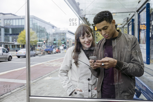 Couple looking at phone in bus stop