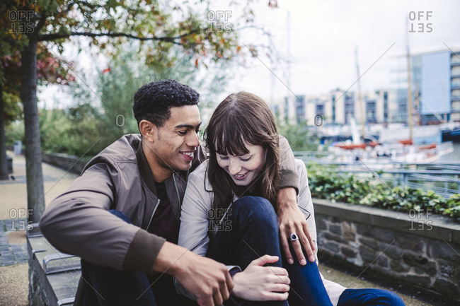 Couple cuddling on bench in city