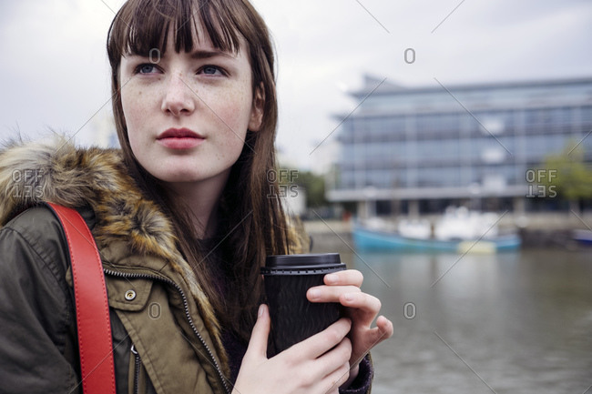 Portrait of young woman by river harbor with coffee