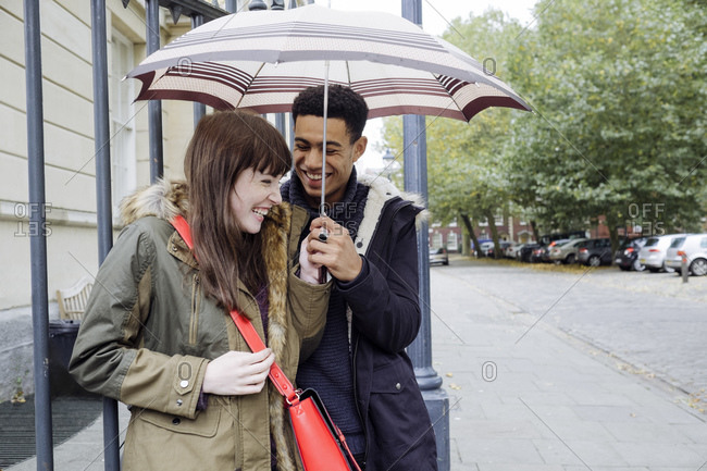 Couple with umbrella at bus stop