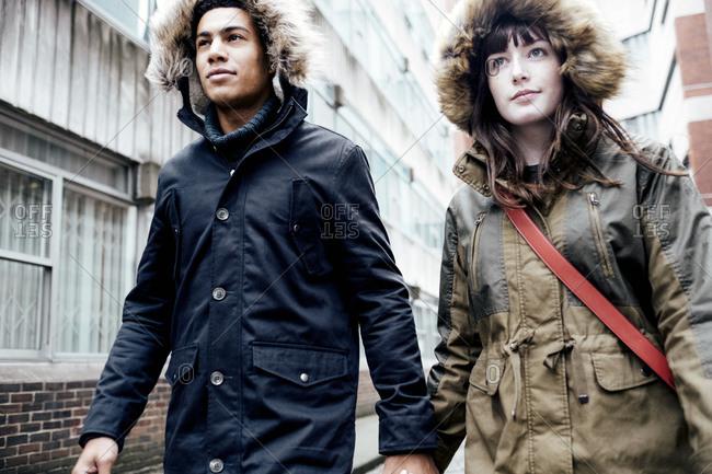 Couple hand in hand walking in narrow street